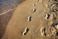 Pasos del pie en la arena de la playa Imagenes de archivo