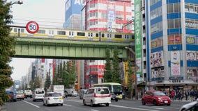 Pasos del tráfico debajo de un puente del carril en una calle principal céntrica ocupada de Tokio un metro pasa sobre el camino o almacen de video