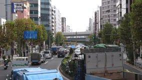 Pasos del tráfico debajo de un puente en una calle principal céntrica ocupada de Tokio Los coches y otros transportes llenan el c almacen de video
