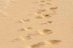 Pasos en la arena caliente. Fotos de archivo