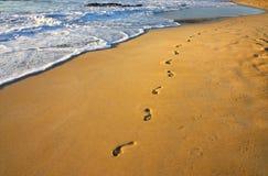 Pasos en la playa y el agua Imagenes de archivo