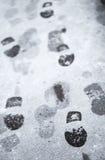 Pasos en nieve mojada en la carretera de asfalto Imagen de archivo libre de regalías