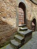 Pasos medievales que llevan a la puerta de madera resistida de un hogar imagenes de archivo