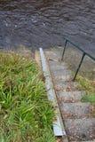 Pasos que llevan abajo a la choza del indicador de agua de río en un alto o un nivel de inundación Imagen de archivo