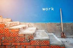 Pasos rojos del ladrillo y de una pala contra la pared Lugar para el texto imagenes de archivo