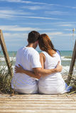 Pasos románticos de la playa de los pares del hombre que se sientan y de la mujer Foto de archivo libre de regalías
