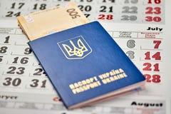 paspoort met de dichte omhooggaande mening van het nationale valutapapiergeld van contant geld op een kalenderachtergrond stock foto's