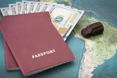 Paspoort met honderd dollarsrekeningen binnen en stuk speelgoed auto op bac stock afbeelding