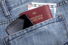 Paspoort, mobiel telefoon en geld in zak Stock Afbeeldingen