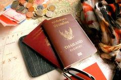 Pasport med symbolerna av Thailand och Republique francaise och några mynt på världskarta Royaltyfria Foton