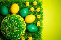 Pasqua che celebra dolce su erba verde con i polli gialli del giocattolo fotografia stock libera da diritti