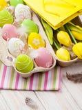 Pasqua con i tulipani gialli, le uova variopinte ed il regalo insaccano Fotografia Stock