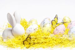 Pasqua felice Coniglietto bianco di Pasqua su un fondo bianco con le uova di Pasqua Cartolina d'auguri di Pasqua con il conigliet fotografie stock