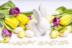 Pasqua felice Coniglietto bianco di Pasqua su un fondo bianco con le uova di Pasqua ed i tulipani freschi Cartolina d'auguri di P immagine stock libera da diritti