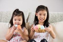 Pasqua felice! Due piccoli bambini svegli che si siedono sul sof? con le uova di Pasqua nel nido o nel canestro immagine stock