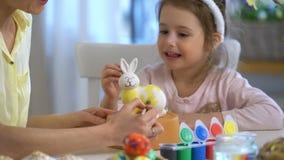 Pasqua felice! Generi e sua figlia con le orecchie del coniglietto che dipingono il coniglietto di pasqua video d archivio