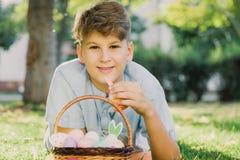 Pasqua felice! L'adolescente sorridente sveglio del ragazzo in camicia blu tiene il canestro con le uova colorate fatte a mano su fotografia stock