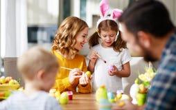 Pasqua felice! la madre, il padre ed i bambini della famiglia dipingono le uova per la festa fotografie stock