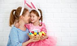 Pasqua felice! madre della famiglia e figlia del bambino con il GE della lepre delle orecchie fotografia stock