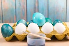 Pasqua felice, uova di Pasqua blu organiche con le uova bianche di colore aspetta la verniciatura, decorazioni di festa di pasqua Fotografia Stock