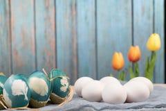 Pasqua felice, uova di Pasqua organiche aspetta la verniciatura con le uova di Pasqua blu, le decorazioni di festa di pasqua, amb immagini stock libere da diritti