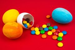 Pasqua felice Uovo di Pasqua rotto con delle le decorazioni colorate multi della caramella su fondo rosso Copi lo spazio per test Fotografia Stock Libera da Diritti