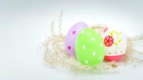 Pasqua felice, uovo di Pasqua variopinto sugli ambiti di provenienza bianchi, decorazioni di festa di pasqua, ambiti di provenien Fotografia Stock Libera da Diritti