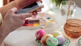 Pasqua, feste, tradizione, tecnologia e concetto della gente - vicino su delle mani della donna con lo smartphone che prende imma archivi video