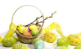 Pasqua ha colorato le uova con un canestro delle viti fotografie stock