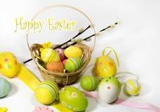 Pasqua ha colorato le uova con un canestro delle viti fotografie stock libere da diritti