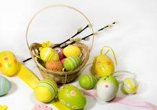 Pasqua ha colorato le uova con un canestro delle viti fotografia stock