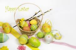 Pasqua ha colorato le uova con un canestro delle viti immagine stock