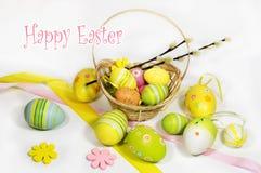Pasqua ha colorato le uova con un canestro delle viti immagini stock libere da diritti