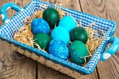 Pasqua ha colorato le uova, paglia, fiori Fotografie Stock