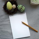 Pasqua ha decorato le uova in nido, blocco note di carta in bianco su fondo grigio immagine stock libera da diritti