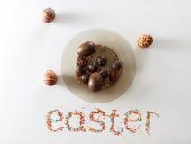 Pasqua ha fatto dall'uva passa e lo zucchero variopinto di cottura sopra fondo bianco con un piatto pieno delle uova di cioccolat Fotografia Stock