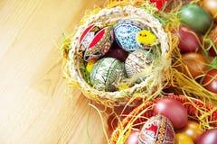 Pasqua ha verniciato le uova in cestino tradizionale Fotografia Stock