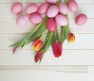 pasqua Le uova di Pasqua ed i tulipani rosa si trovano su un fondo di legno Disposizione piana Immagine Stock