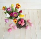 pasqua Le uova di Pasqua ed i tulipani rosa si trovano su un fondo di legno Disposizione piana Fotografie Stock Libere da Diritti