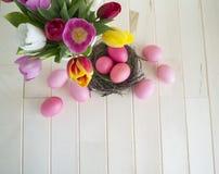 pasqua Le uova di Pasqua ed i tulipani rosa si trovano su un fondo di legno Disposizione piana Fotografia Stock