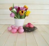 pasqua Le uova di Pasqua ed i tulipani rosa si trovano su un fondo di legno Disposizione piana Fotografia Stock Libera da Diritti