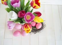 pasqua Le uova di Pasqua ed i tulipani rosa si trovano su un fondo di legno Disposizione piana Immagini Stock