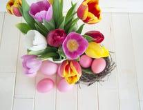 pasqua Le uova di Pasqua ed i tulipani rosa si trovano su un fondo di legno Disposizione piana Immagini Stock Libere da Diritti