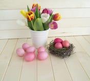 pasqua Le uova di Pasqua ed i tulipani rosa si trovano su un fondo di legno Disposizione piana Fotografie Stock