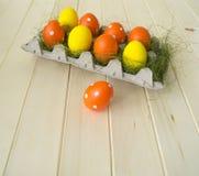 pasqua Le uova di Pasqua sono gialle ed arancio Bugia delle uova nel contenitore per le uova Erba verde Immagine Stock