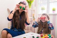 Pasqua - occhi divertenti della figlia e della madre che le uova Fotografie Stock Libere da Diritti