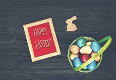 Pasqua, uova di Pasqua, uova multicolori, canestro, fondo nero fotografia stock libera da diritti
