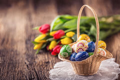 pasqua Uova di Pasqua dipinte fatte a mano merce nel carrello e tulipani della molla Immagine Stock