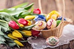 pasqua Uova di Pasqua dipinte fatte a mano merce nel carrello e tulipani della molla Fotografie Stock Libere da Diritti