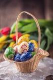 pasqua Uova di Pasqua dipinte fatte a mano merce nel carrello e tulipani della molla Immagine Stock Libera da Diritti